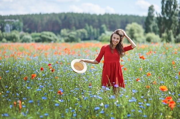 Linda jovem romântica com chapéu de palha no campo de flores de papoula Foto Premium