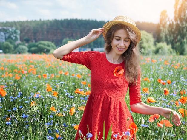 Linda jovem romântica no chapéu de palha no campo de flor papoula