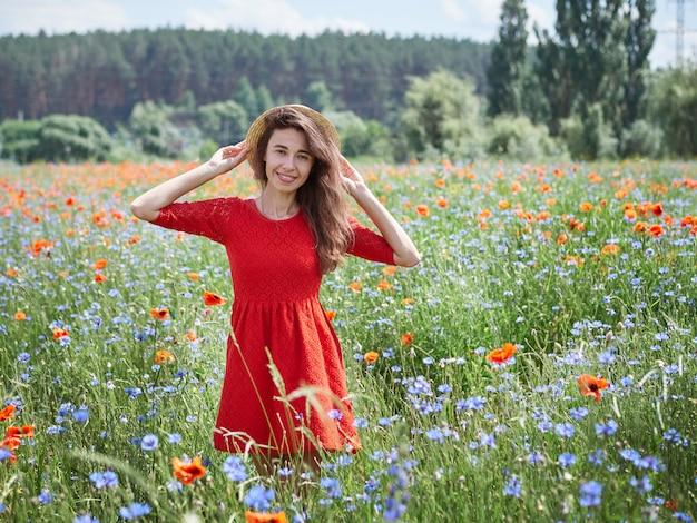Linda jovem romântica no chapéu de palha no campo de flores de papoula, posando no verão de fundo