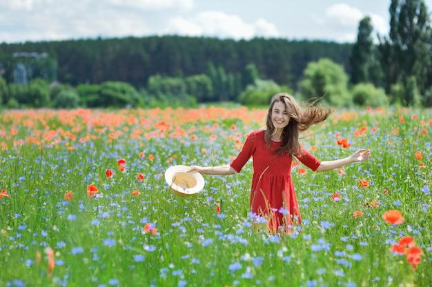 Linda jovem romântica no chapéu de palha no campo de flores de papoula
