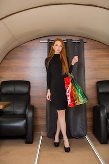 Linda jovem ruiva com pacotes nas mãos em um avião particular