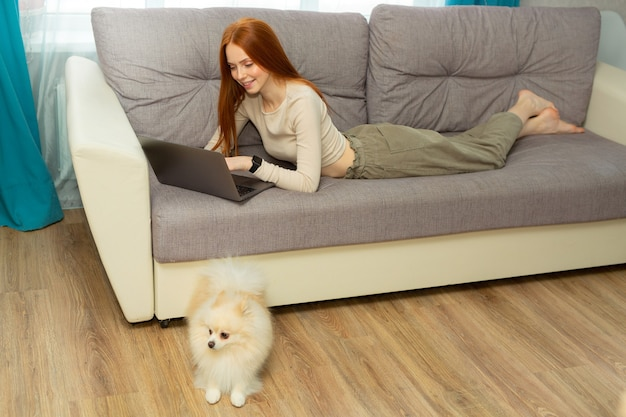 Linda jovem ruiva deitada em casa no sofá com um laptop