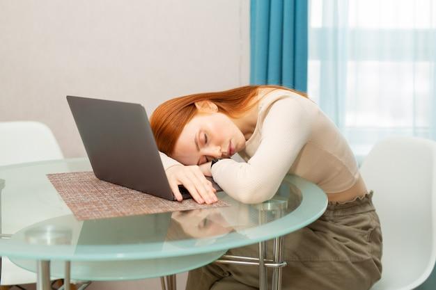 Linda jovem ruiva dormindo à mesa com um laptop