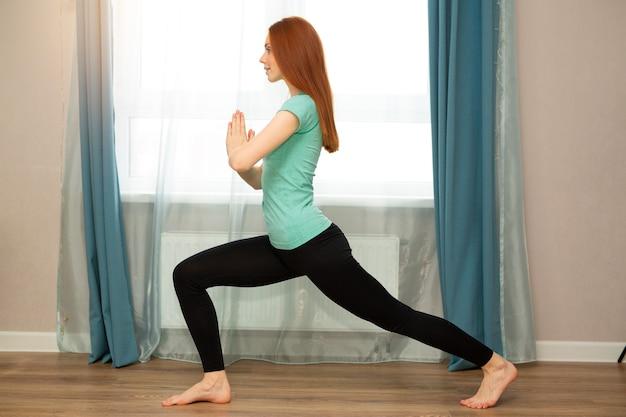 Linda jovem ruiva fazendo ioga em casa