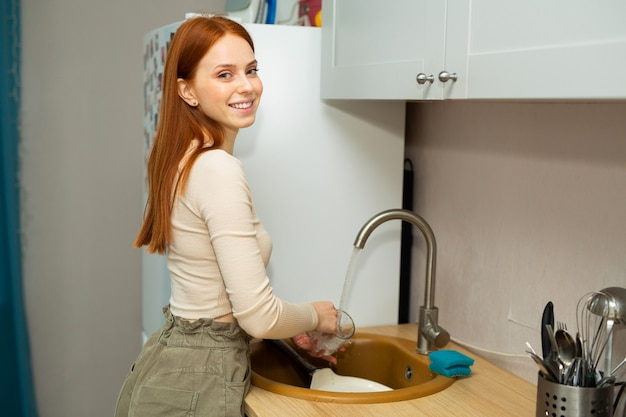 Linda jovem ruiva lava a louça
