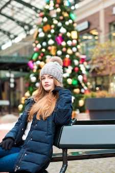 Linda jovem ruiva vestindo roupa de inverno, posando no fundo de um abeto de natal
