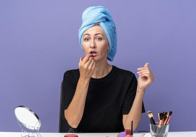 Linda jovem se senta à mesa com ferramentas de maquiagem, enxugando o cabelo na toalha e aplicando batom isolado na parede azul