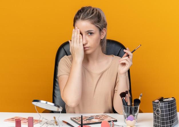 Linda jovem se senta à mesa com ferramentas de maquiagem, segurando o pincel de maquiagem e o olho coberto com a mão isolada na parede laranja