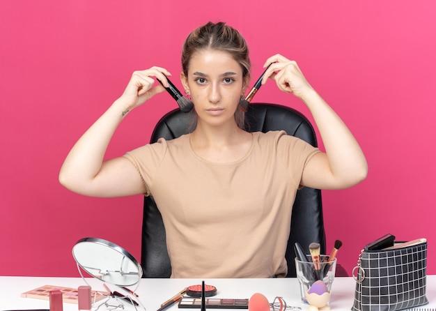 Linda jovem se senta à mesa com ferramentas de maquiagem segurando um pincel em torno do rosto isolado na parede rosa