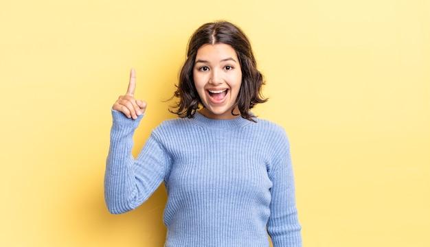Linda jovem se sentindo um gênio feliz e animado depois de realizar uma ideia, levantando o dedo alegremente, eureka!