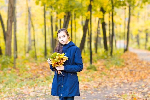 Linda jovem segurando folhas amarelas no parque outono