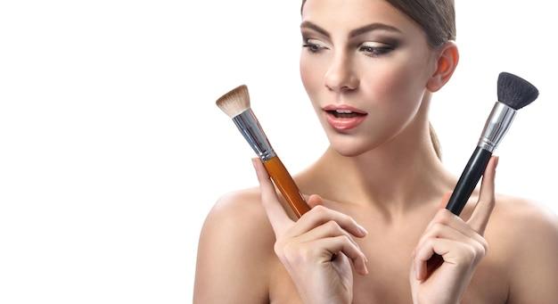 Linda jovem segurando pincéis de maquiagem isolados no branco