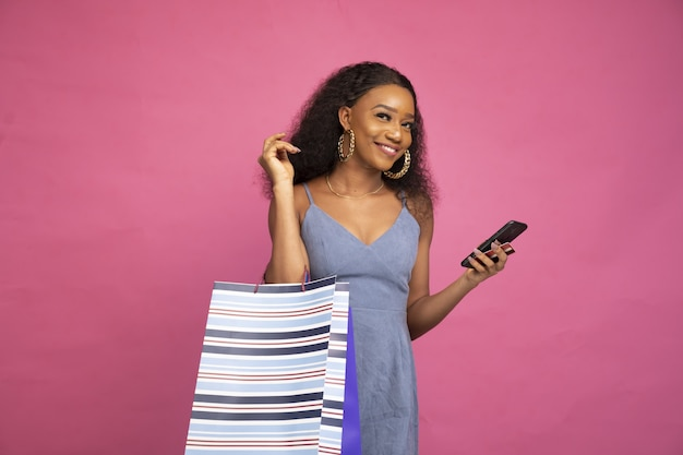 Linda jovem segurando sacolas de compras usando seu telefone celular