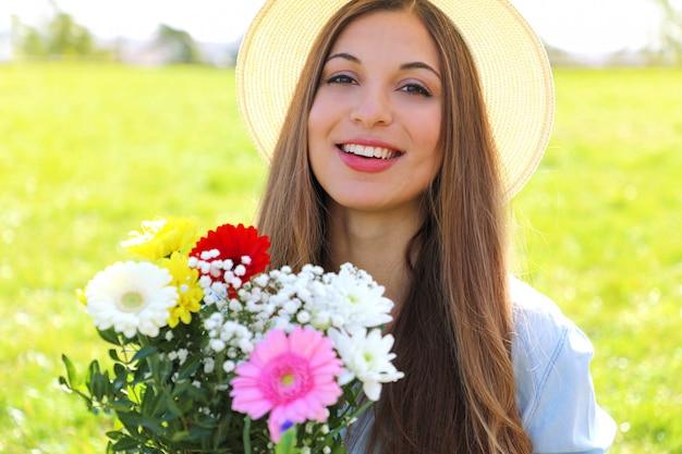 Linda jovem segurando um buquê de flores e olhando para a câmera em um campo na primavera