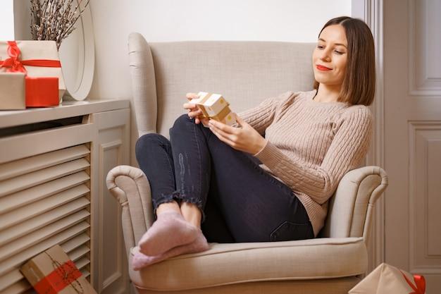 Linda jovem sentada em uma poltrona confortável segurando uma caixa de presente rodeada de presentes em casa.