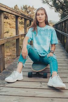 Linda jovem sentado em um longboard em tempo ensolarado