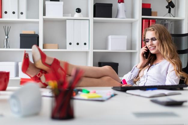 Linda jovem sentado em uma cadeira, jogando as pernas em cima da mesa e falando ao telefone
