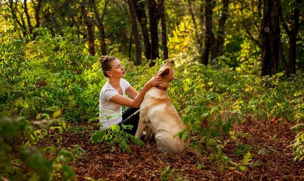 Linda jovem sentado na floresta com um cachorro e acariciando seu amado animal de estimação