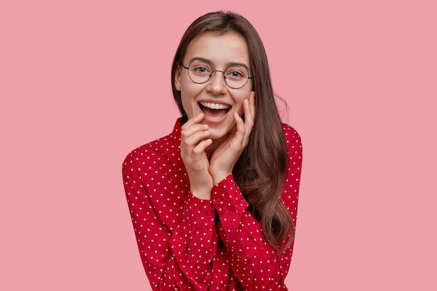 Linda jovem sorri positivamente, mostra dentes brancos perfeitos, tem uma pele macia e saudável, vestida com uma camisa de bolinhas