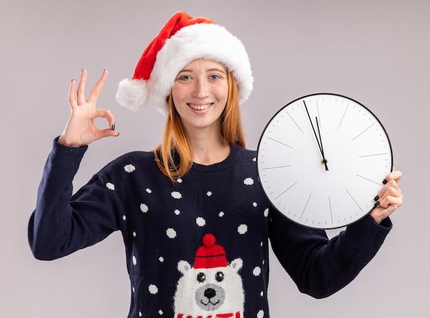 Linda jovem sorridente com chapéu de natal segurando um relógio de parede e mostrando um gesto de ok isolado na parede branca