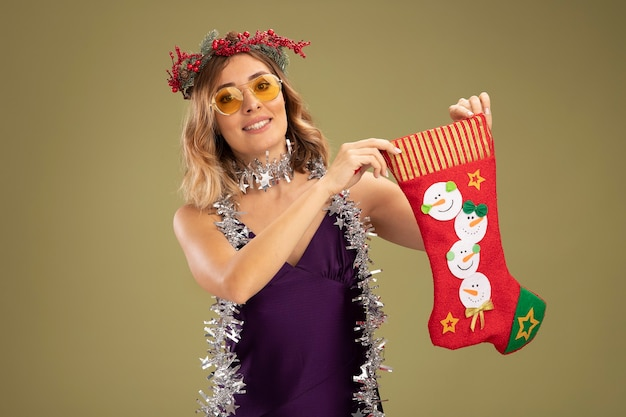 Linda jovem sorridente com vestido roxo e grinalda com óculos e guirlanda no pescoço segurando uma meia de natal isolada em fundo verde oliva