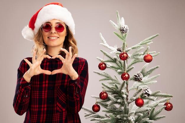 Linda jovem sorridente em pé perto da árvore de natal, usando chapéu de natal e óculos, mostrando um gesto de coração isolado no fundo branco