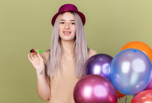Linda jovem sorridente usando aparelho dentário com chapéu de festa em pé perto de balões segurando o apito isolado na parede verde oliva