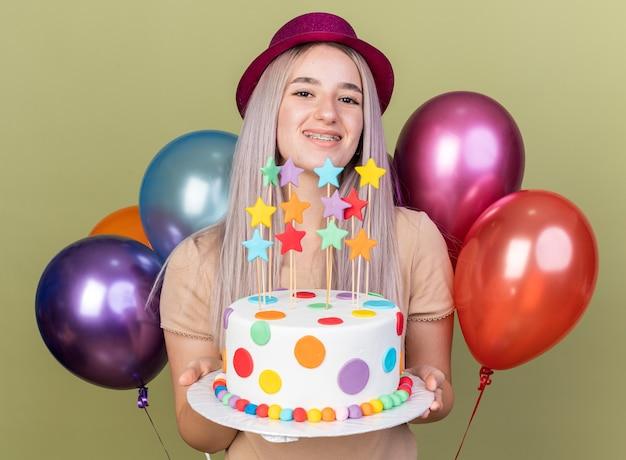 Linda jovem sorridente usando aparelho dentário com chapéu de festa segurando um bolo em pé na frente de balões