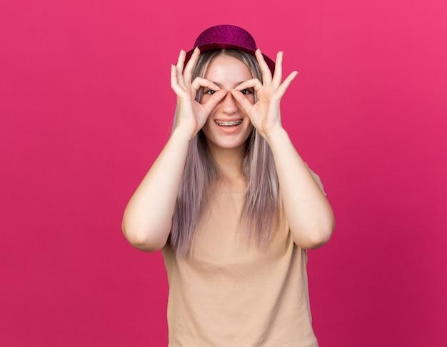Linda jovem sorridente usando chapéu de festa com aparelho dentário mostrando gesto de olhar isolado na parede rosa