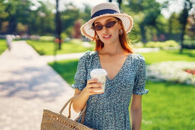 Linda jovem sorrindo caminhando no parque segurando bolsa de palha e café em copo descartável ...