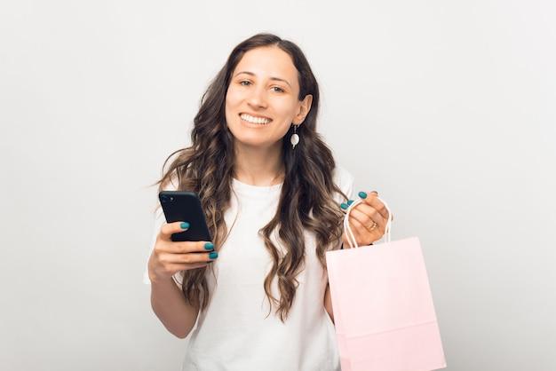 Linda jovem sorrindo para a câmera está segurando uma sacola de compras rosa claro e o telefone dela.