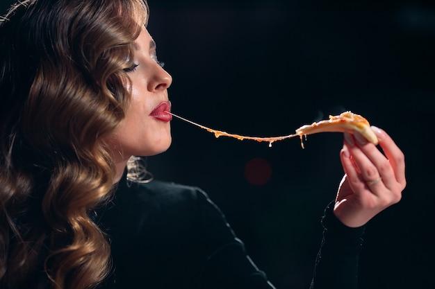 Linda jovem sozinha comendo pizza em um restaurante
