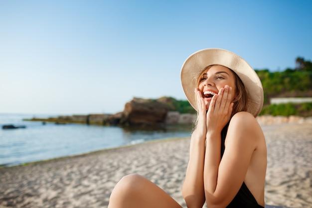 Linda jovem surpresa no chapéu repousa na praia de manhã