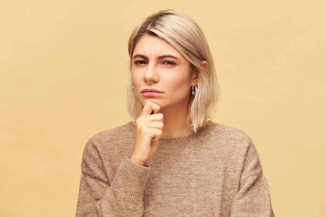 Linda jovem suspeita feminina na moda europeia em um pulôver de caxemira, segurando a mão em seu queixo e olhando com suspeita e desconfiança, franzindo os olhos. expressões faciais humanas