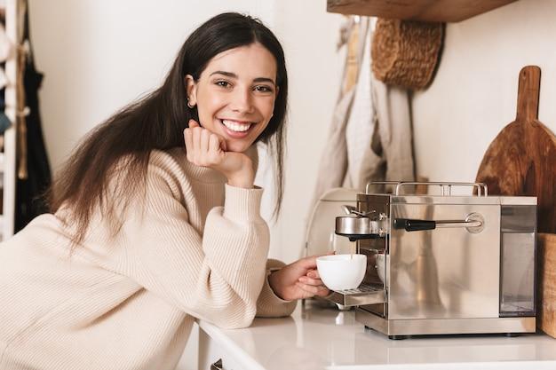 Linda jovem tomando uma xícara de café na cozinha, usando a máquina de café