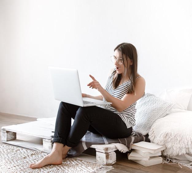 Linda jovem trabalha remotamente atrás de um laptop em casa. o conceito de freelancer e de trabalhar na internet.