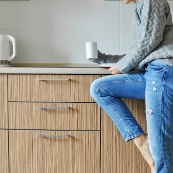 Linda jovem trabalhando e bebendo café em uma cadeira na cozinha no estilo escandinavo.