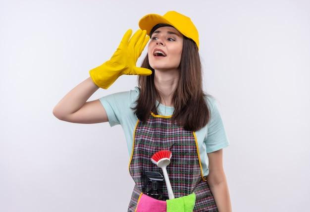 Linda jovem usando avental, boné e luvas de borracha, gritando ou gritando com a mão perto da boca