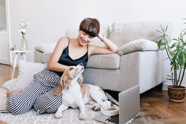 Linda jovem usando calças listradas e relógio de pulso posando no chão enquanto brinca com o cachorro beagle