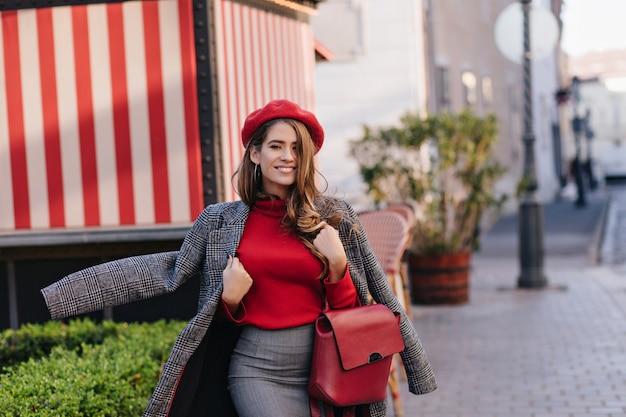 Linda jovem usando saia cinza e casaco andando pela rua no início da noite e sorrindo