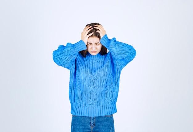 Linda jovem vestindo um suéter azul de mãos dadas na cabeça.