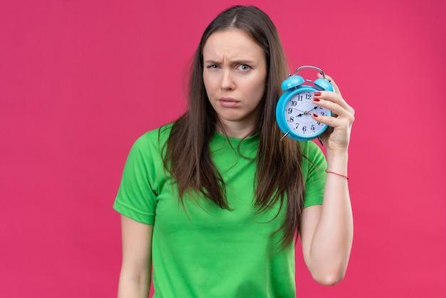 Linda jovem vestindo uma camiseta verde segurando um despertador, olhando para a câmera com uma expressão cética no rosto em pé sobre um fundo rosa isolado