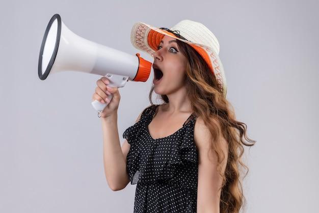 Linda jovem viajante com vestido de bolinhas e chapéu de verão gritando para o megafone surpresa e chocada em pé sobre um fundo branco