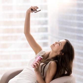 Linda lade na poltrona fazendo selfie