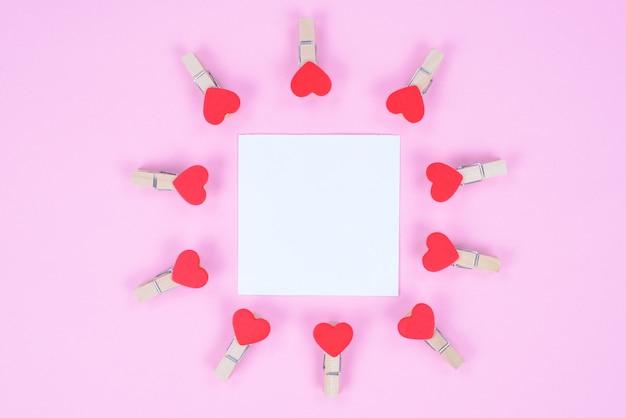 Linda linda decoração artesanal artesanal diy para o conceito de férias românticas. foto com vista de alto ângulo de uma folha de papel sem texto e pequenos prendedores de roupa isolados