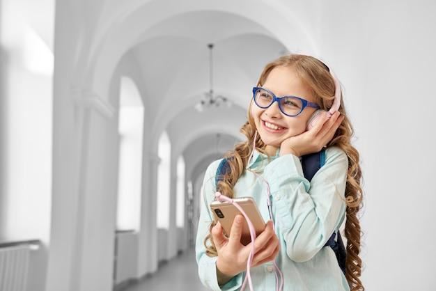 Linda, linda e positiva colegial ouvindo música com fones de ouvido durante as férias escolares.