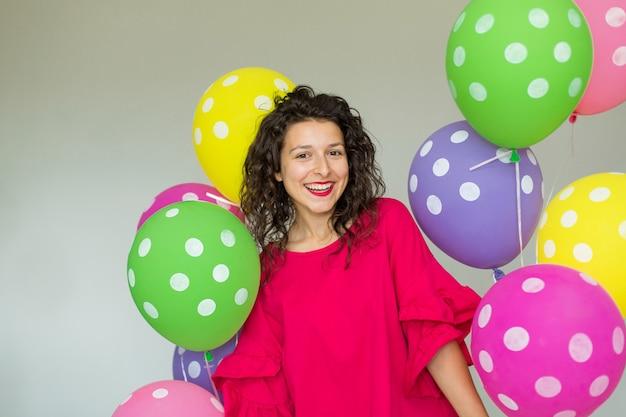 Linda linda garota alegre com balões coloridos. feliz aniversário de férias.