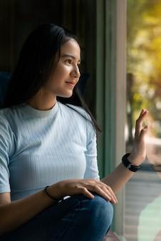 Linda linda garota asiática sentado e sorrindo no café perto da janela. cabelo comprido preto feliz mulher asiática na camisa azul. pessoas bonitas e conceito da moda