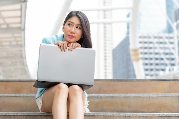 Linda linda garota com roupas de mulher de negócios, usando o computador laptop, segundo plano urbano da cidade de negócios