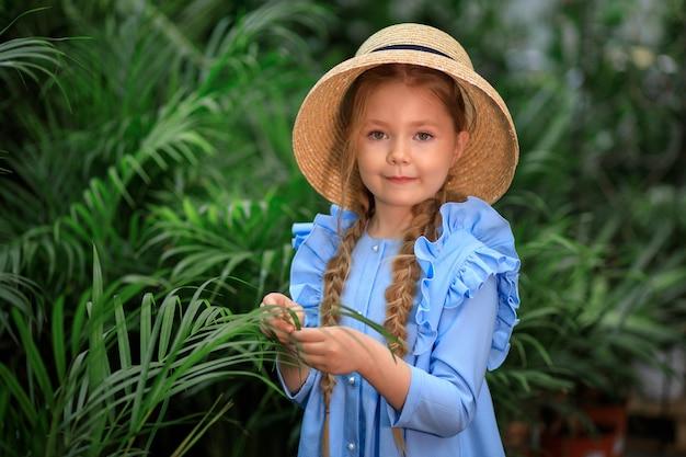 Linda linda garota com um chapéu de palha em uma estufa perto de plantas verdes